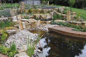 A pond, rocks and small seating area in a Hampshire garden designed by Martyn Gingell