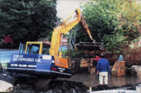Supervising placement of rocks around a pond by garden designer Hampshire Martyn Gingell